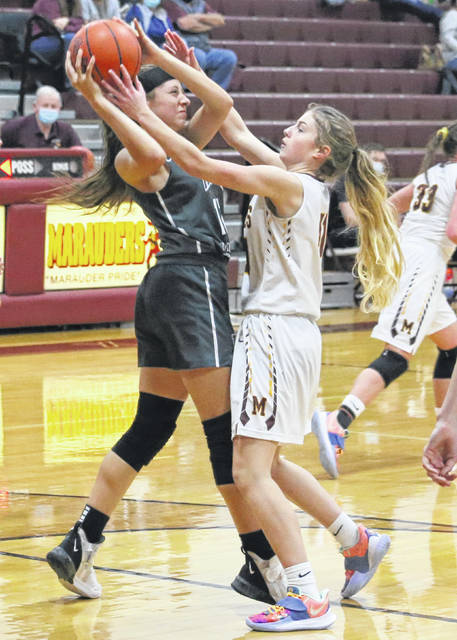 River Valley junior Morrisa Barcus, left, fends off Meigs freshman Maggie Musser after hauling in a rebound during the first half of Monday night's girls basketball game at Larry R. Morrison Gymnasium in Rocksprings, Ohio.