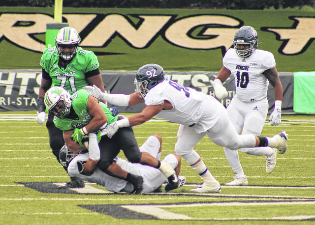Marshall running back Brenden Knox is pulled down to the ground by a pair of Rice defenders during Saturday's Conference USA football game at Joan C. Edwards Stadium in Huntington, W.Va.