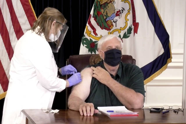 In this image made from video released by the State of West Virginia, a nurse administers a coronavirus shot to west Virginia Gov. Jim Justice, Monday, Dec. 14, 2020, in Charleston, W.Va. The 69-year-old Republican governor said he would receive a shot before cameras which would make him one of the first top elected officials in the country to get vaccinated. Officials said they want to demonstrate their confidence in the vaccine. (State of West Virginia via AP)