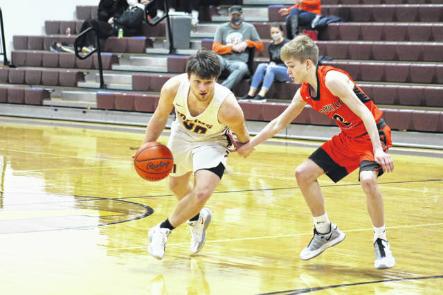 Meigs junior Jake McElroy (left) drives past Nelsonville-York's James Koska (right), during the fourth quarter of the Marauders' 72-47 victory on Tuesday in Rocksprings, Ohio.