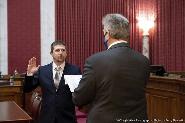 West Virginia House of Delegates member Derrick Evans, left, is given the oath of office Dec. 14, 2020, in the House chamber at the state Capitol in Charleston, W.Va. Evans recorded video of himself and fellow supporters of President Donald Trump storming the U.S. Capitol in Washington, D.C., on Wednesday, Jan. 6, 2021 prompting calls for his resignation and thousands of signatures on an online petition advocating his removal. (Perry Bennett/West Virginia Legislature via AP)