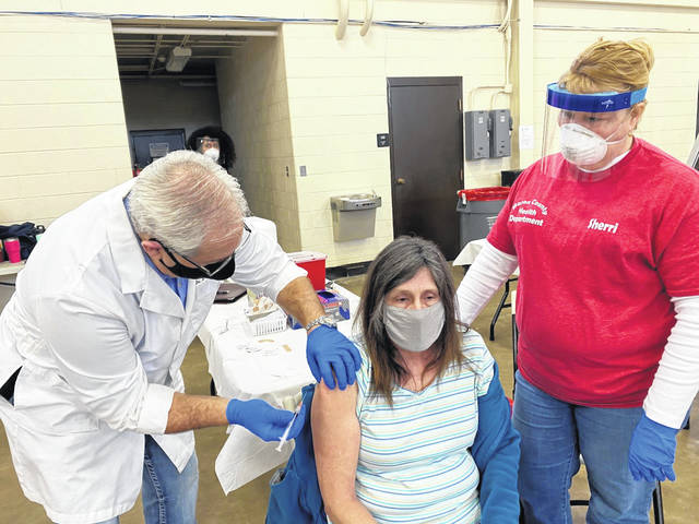 Pictured is Teresa Smith receiving the COVID-19 vaccine from PVH ER physician Dr. Daniel Trent and Sherri Nutter, RN, with the Mason County Health Department. (PVH   Courtesy)