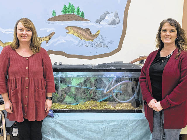 Teachers Jacque Richardson, left, and Shayla Blackshire are pictured in front of the fish tank located in the Trout in the Classroom lab at New Haven Elementary School. The two recently received a grant to enhance the program and allow daily video updates for both the students and the public. (Courtesy photo)