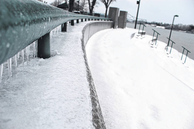 Ice collects along the beams and railing at Point Pleasant Riverfront Park on Tuesday evening along the Ohio River. Ice has collected on trees and roadways in recent days, causing headaches for residents who have lost power, motorists and DOH crews. (Beth Sergent | OVP)
