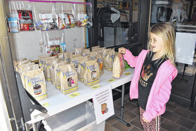 """Kabella Ord is pictured as she chooses a """"Grab and Go Lunch"""" at one of the Mason County libraries during the summer. Once an indoor event, the summer lunch program was moved to outside the library doors or inside the vestibule so the program could continue during the COVID-19 pandemic."""