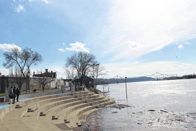 Visitors to Riverfront Park in Point Pleasant observe the Ohio River overtake the amphitheater on Monday afternoon. (Beth Sergent | OVP)