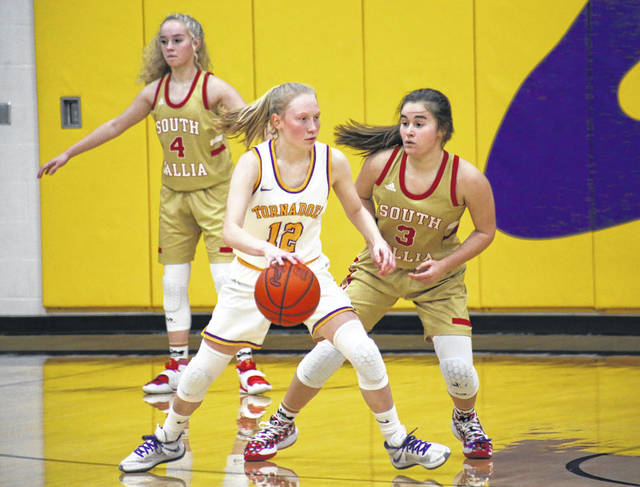 Southern junior Kayla Evans (12) dribbles near the top of the key, while South Gallia freshmen Tori Triplett (3) and Macie Sanders (4) play defense, during the Lady Rebels' Dec. 30, 2020, victory in Racine, Ohio.