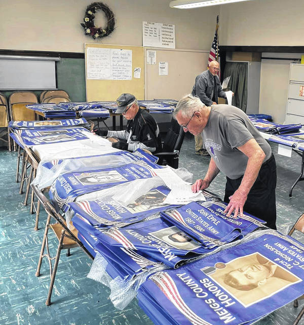Meigs County Armed Forces Banner Project committee members sort banners to be placed in communities around the county.