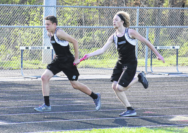 River Valley's Kade Alderman takes the baton from Nathan Young in the final exchange of the 4x200m relay on April 13 in Bidwell, Ohio.