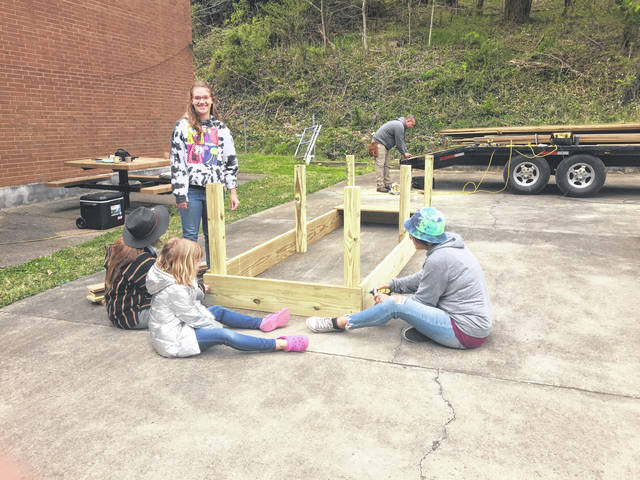 The Rife family made building the garden beds a family affair. Pictured are Halo, Phoebe, Olivia and Stephanie working on one of the beds, Sam Rife in the background unloading wood.