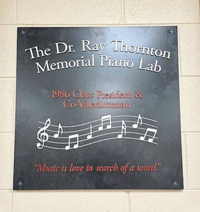"""Currently displayed at Point Pleasant Junior/Senior High School, this plaque denotes """"The Dr. Ray Thornton Memorial Piano Lab. 1986 Class President & Co-Valedictorian. Music is love in search of a word."""""""