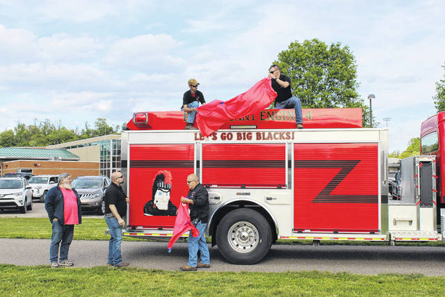 """Members of the Point Pleasant Fire Department unveil the new Engine Four, also known as """"The Big Blacks Edition"""" featuring a custom depiction of the PPJ/SHS Black Knight and the wording, """"Let's Go Big Blacks!"""""""