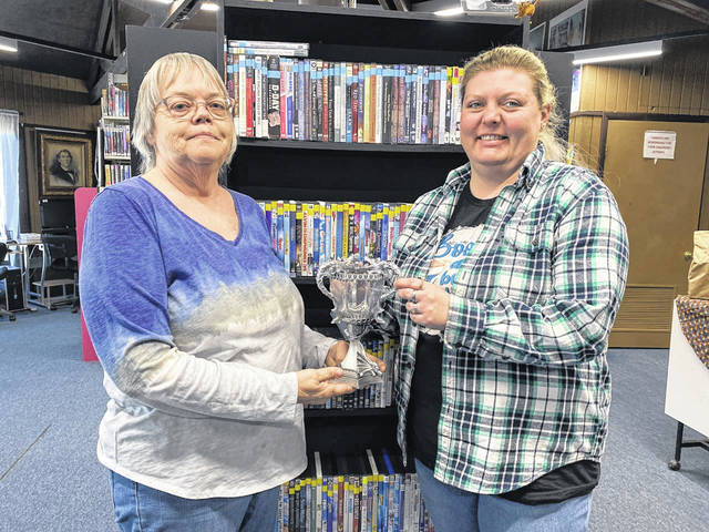 """Mason County Library Director Pam Thompson, left, and Librarian April Scott, are pictured with the trophy the winner of the Mason County Tri-Wizard Tournament will receive on Sat., July 31, as part of the Summer Reading Program. This year's theme is """"Imagine Your Story,"""" and will be held in person."""