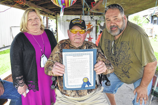 """It was """"Bill McFarland Day"""" in the Town of New Haven Tuesday, as the World War II Navy veteran marked his 100th birthday. He is pictured with the proclamation, and flanked by Recorder Becky Benson, left, and Mayor Phil Serevicz."""