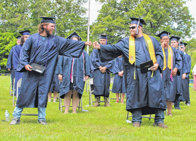 Hannan seniors Chase Poore, left, and Skyler Nance share a fist-bump shortly after being announced as official graduates on Saturday at the 2021 graduation ceremony held at HHS in Ashton.