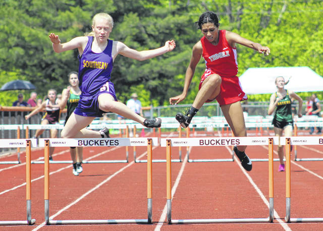 Southern junior Kayla Evans, left, clears the final obstacle during the 300m hurdles final on Saturday at the D-3 District Track and Field Championships held at Nelsonville-York High School in Nelsonville, Ohio.