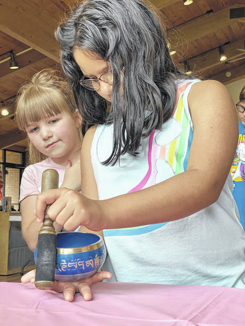The Mason County Library Summer Reading Program has kept local children busy, including these two vistors to the New Haven Library, trying their hand at playing the Tibetan singing bowl.