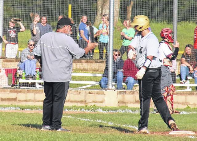 River Valley head coach Bobby Jeffers (left) congratulates Isiah Harkins (right) on a game-tying RBI single, during the Raiders' 2-1 win over Vinton County on May 5 in Bidwell, Ohio.