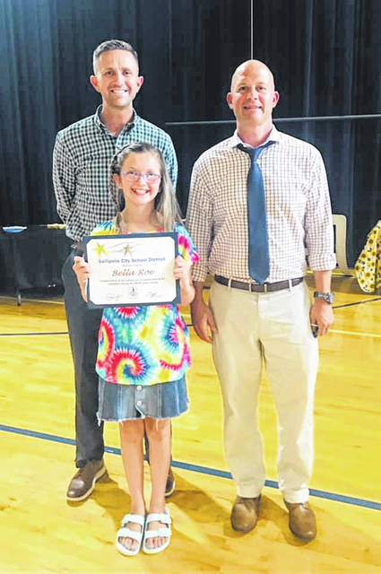 Bella Roe, pictured center, was recognized during a district board of education meeting for reading aloud every day through the pandemic. Also pictured, from left are Principal Corey Luce and Superintendent Craig Wright.