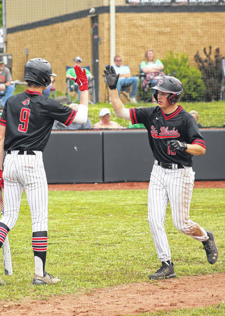 Point Pleasant senior Isaac Craddock, right, gets a high-five from teammate Kyelar Morrow after scoring in the third inning Tuesday night in a Class AA Region IV, Section 1 baseball game against Winfield in Point Pleasant, W.Va.
