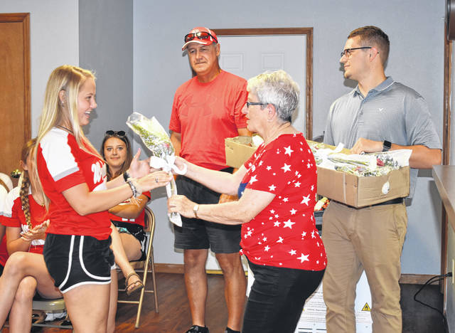 The Mason United Methodist Church, represented by Kathy VanMeter, gave each of the girls a red and white flower bouquet. Bailee Bumgarner is pictured receiving hers from VanMeter, with Noble and Mayor Clark in the background.