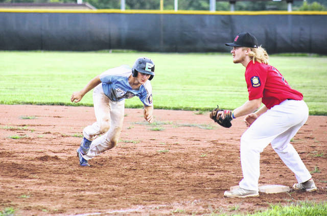 Colton Reynolds (left) dives back into first base on a pickoff attempt, during Tuesday's game in Rocksprings, Ohio.