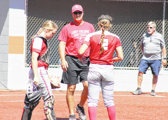 Wahama softball coach Chris Noble joins catcher Amber Wolfe, left, at the circle to talk strategy with pitcher Mikie Lieving (2) during the Class A championship game against Ritchie County on June 23 at Craft Field in South Charleston, W.Va.