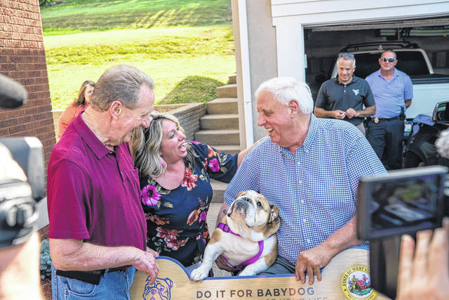 Wally Board of Spencer, (pictured far left), is presented a cermonial check for $1.5 million dollars by Gov. Jim Justice and Babydog earlier this week.