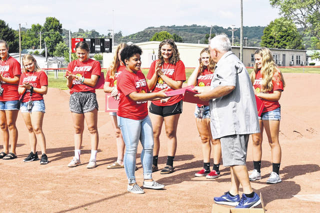 Wahama Lady Falcons Softball player Aleisia Barnitz is pictured as she receives a certificate of recognition by Mason County Commission President Sam Nibert Sunday, as a few other members of the team look on. Nibert and fellow Commissioner Rick Handley hosted a ceremony at the softball field in Hartford to honor the team, which won the Class A State Championship earlier this summer. Commissioner Tracy Doolittle was unable to attend.