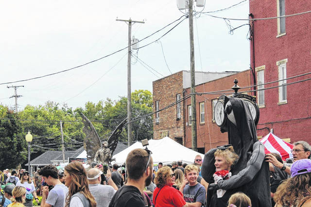 Pictured is a scene from a previous Mothman Festival with the Mothman statue in Point Pleasant visible just past the sea of people along Main Street.