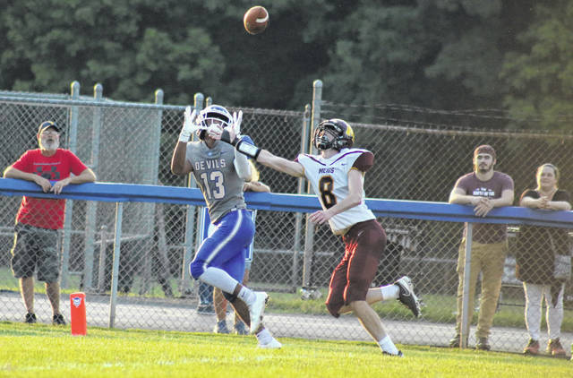 Gallia Academy sophomore Kenyon Franklin (13) hauls in a touchdown pass over Meigs' cornerback Wes Metzger (8) during the first quarter of the Blue Devils' 22-19 victory on Friday in Gallipolis, Ohio.