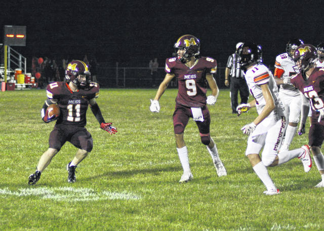 Meigs receiver Jake McElroy (11) prepares to elude a pair of Belpre defenders during the second half of Friday night's Week 2 football contest at Farmers Bank Stadium in Rocksprings, Ohio.