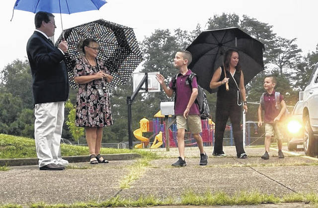 Principal Timothy Click, Vice-principal Judy Browning and Gym Teacher Amy Graham greet smiling students at Roosevelt Elementary School.
