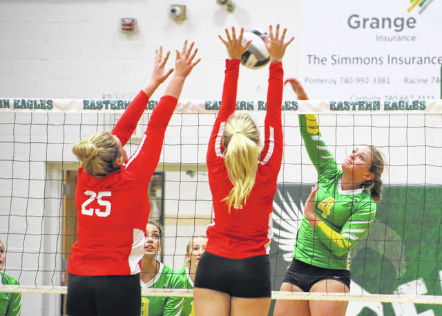 Eastern junior Megan Maxon (4) hits a spike attempt as South Gallia defenders Ryleigh Halley (25) and Emma Clary go for the block during Tuesday night's TVC Hocking volleyball match in Tuppers Plains, Ohio.