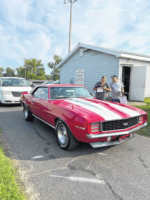 Mike and Melony Baily register cars as they enter the grounds for the 17th annual Crusin' Saturday Night Car Show in Racine, Ohio.