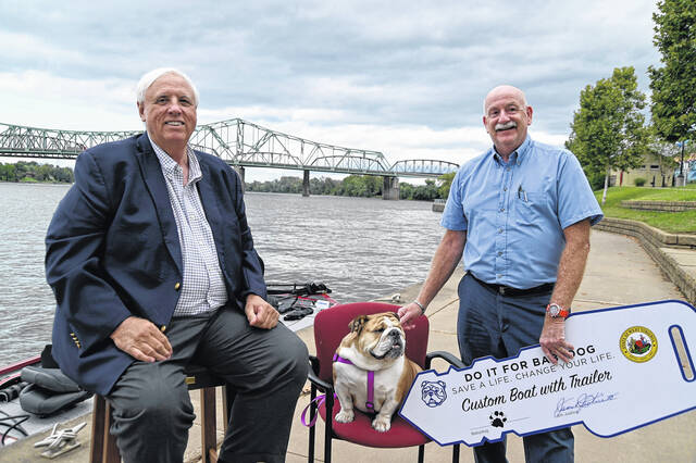 Pictured in Parkersburg is Gov. Jim Justice and Babydog, along with Bruce Kesterson of Davisville, who was presented the keys to a Tracker Pro Team 195 TXW Bass Boat, complete with a GPS fish tracker, FourStroke Mercury 150L Pro XS motor, and an accompanying trailer.