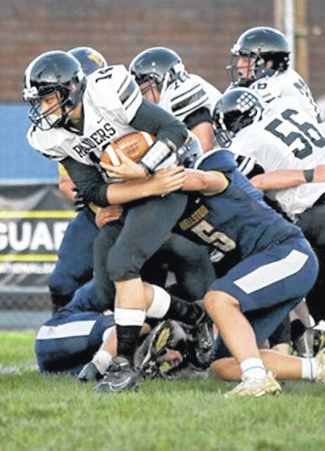 River Valley senior Ryan Jones (14) tries to pick up some extra yardage while being tackled by a pair of Wellston defenders during Friday night's football game in Wellston, Ohio.