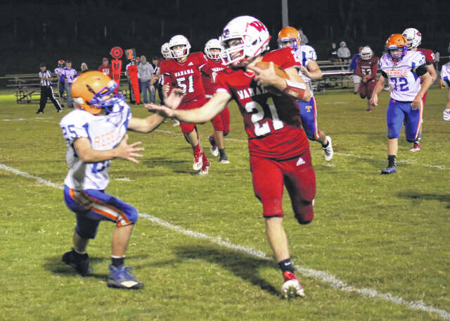 Wahama sophomore Sawyer VanMatre (21) prepares to deliver a stiff arm to a Tolsia defenders during the first half of Friday night's football game at Bachtel Stadium in Mason, W.Va.