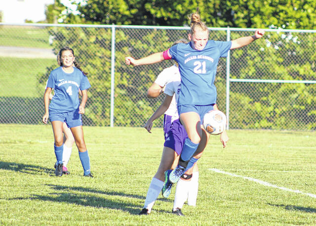 Gallia Academy senior Kyrsten Sanders (21) leaps to control a pass during Thursday's OVC girls soccer match against Chesapeake at Lester Field in Centenary, Ohio.