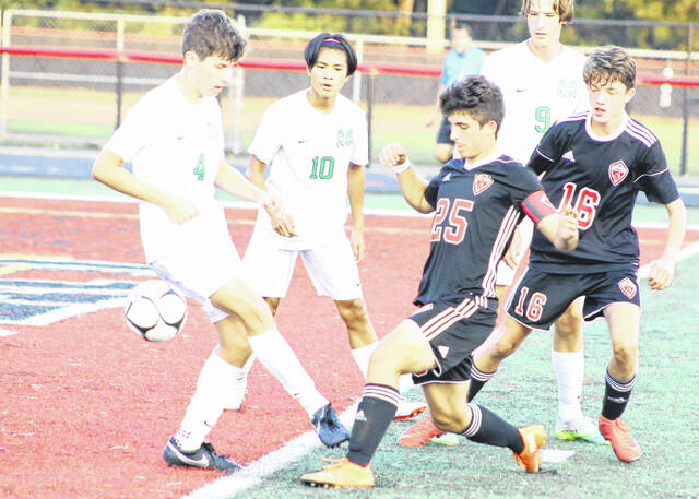 Cael McCutcheon (25) kicks the ball past the Charleston Catholic defense while teammate Cooper Tatterson (16) looks on during a soccer game Tuesday evening in Point Pleasant, W.Va.