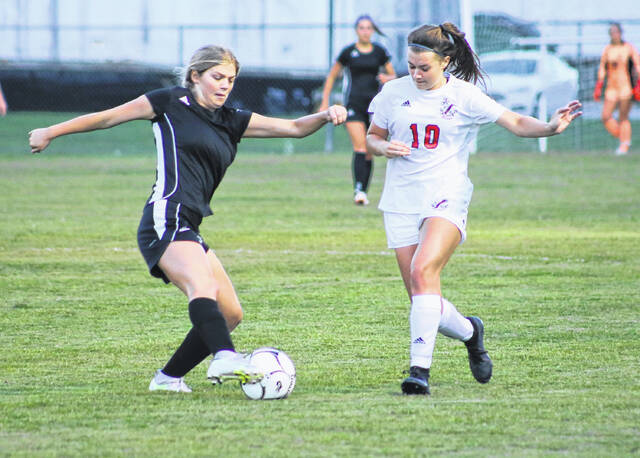 Point Pleasant freshman Reece Oliver (10) works to get the ball away from a Winfield forward during a girls soccer match Thursday evening in Winfield, W.Va.