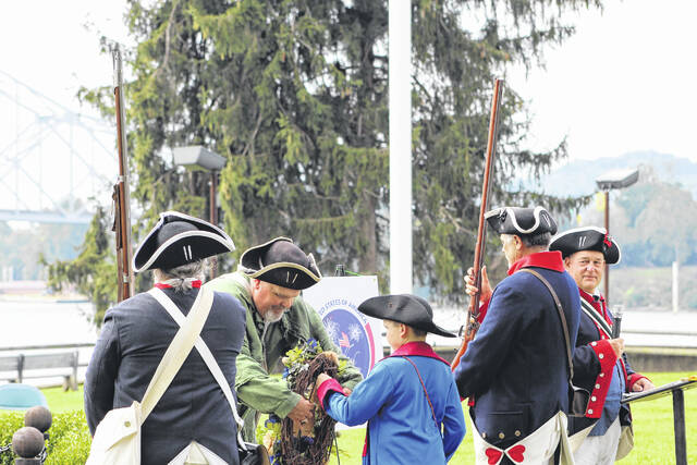 SAR Fort Randolph CAR member Rylan Price presents a wreath at the memorial service for the Battle of Point Pleasant.