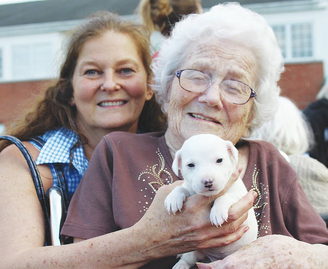 Barb Teter and Elms resident Marvelle Jones hold newly adopted pup Elsa during a dog show at Wellington's Elms Retirement Village.