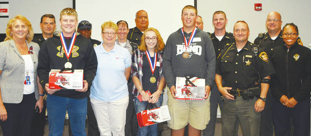 Contest winners Hayden Matus, of Firelands; Alyssa Zurowski, of Midview; and Matthew Rister, of Keystone, are congratulated by JVS staff and law enforcement.