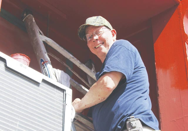 "Longtime Farm & Home Hardware employee Mike Manning helps repaint the front of Wellington Auto Parts Sept. 28 for Main Street Wellington's ""Paint the Town Proud"" initiative."