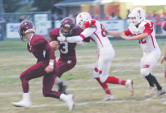 The Dukes' Nathaniel Shelton stiff-arms a Firelands defender Friday night during a 56-26 loss to the Falcons.