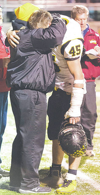 Black River head coach Al Young embraces senior Jacob Campbell after the teams' 40-16 loss Friday to South Range in the Division V Region 17 championship.