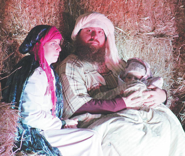 "Mary and Joseph, played by Brooke Galloway and Jonathan Jones, hold newborn baby Jesus on Sunday at Dickson Street Park in the third production of ""The Wondrous Gift."""