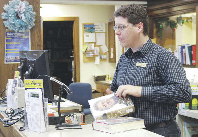 Herrick Memorial Library assistant Nick Blank sorts through returned items Dec. 16. The library will begin a six-month trial Jan. 1 that abolishes all fees on overdue items and forgives past fines as long as the items are returned.