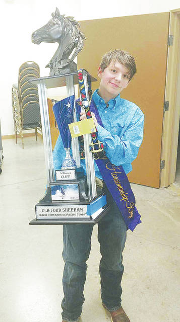 Dakota Miller, 19, holds up his newly-won Clifford Sheehan Senior Gymkhana Revolving Memorial Trophy. It is awarded for a special horsemanship skills competition held on one day during the Lorain County Fair.